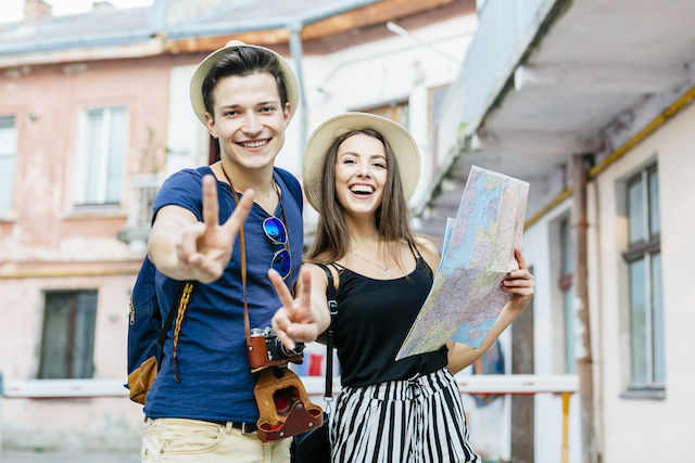 couple giving peace signs with a map walking happily through a town