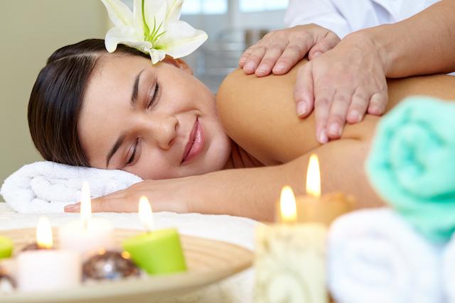 woman smiling enjoying a spa massage.