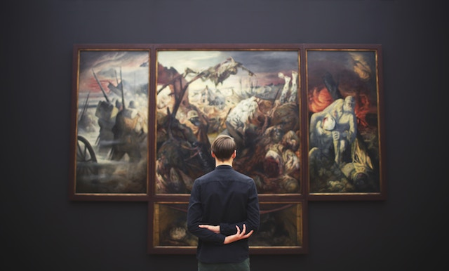 man standing looking at a painting in a museum.