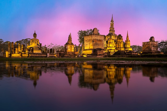 Pink sunset near water and temples in Thailand, a perfect solo spot.