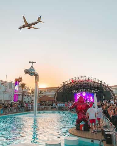 ibiza party with a plane flying over top.
