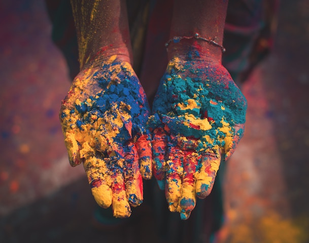 hands holding different dry colors for Holi.
