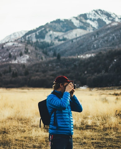 man taking photos in the mountains wearing a roll up puffy jacket, convvenient for packing.