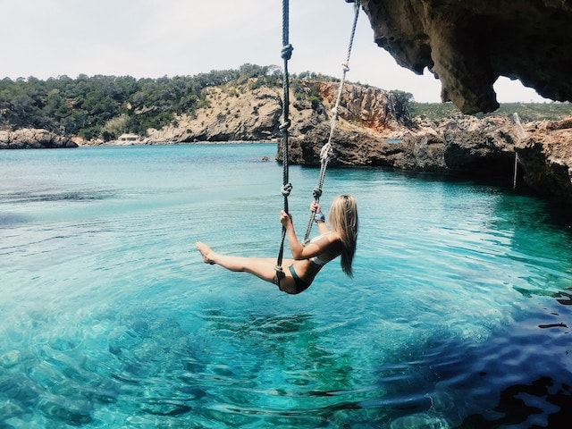 A woman swinging into blue waters in Ibiza, Spain. Great to relax post break up.