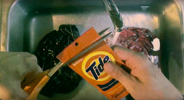 Man cutting and using detergent sink packets to wash clothes.