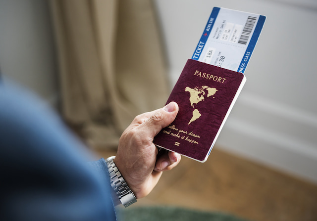person holding a passport and boarding pass ticket, ready to avoid the long wait in security.