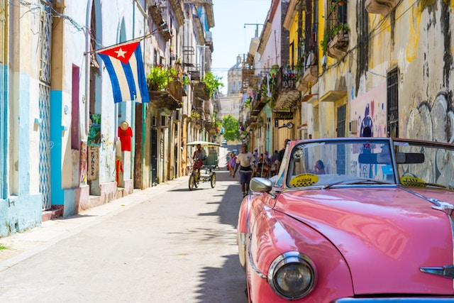 a street of Havana with vintage pink car and many colorful buildings.