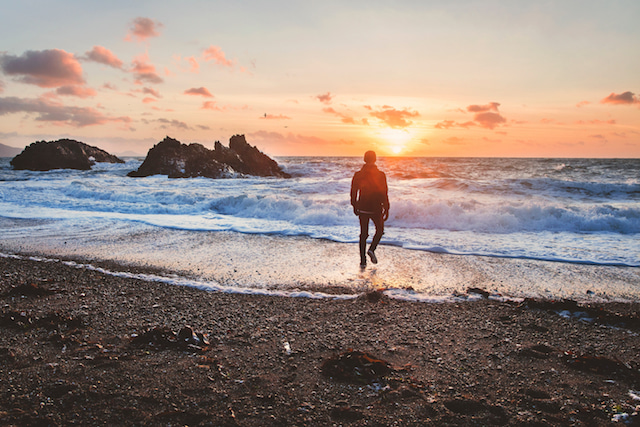 man walking on beach, with zero crowds for the perfect shot during sunrise.