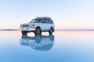 A car on the reflective Salar De Uyuni.