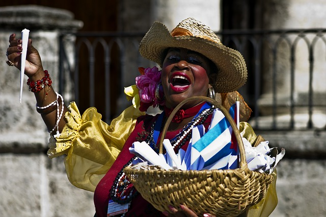 woman handing out souvenirs at a street festival in Havana.