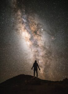 shot atop mauna kea. silhouette of man in front of starry night and the milky way.