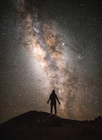 a silhouette of a man in front of a starry night with the milky way. Located atop Mauna Kea.