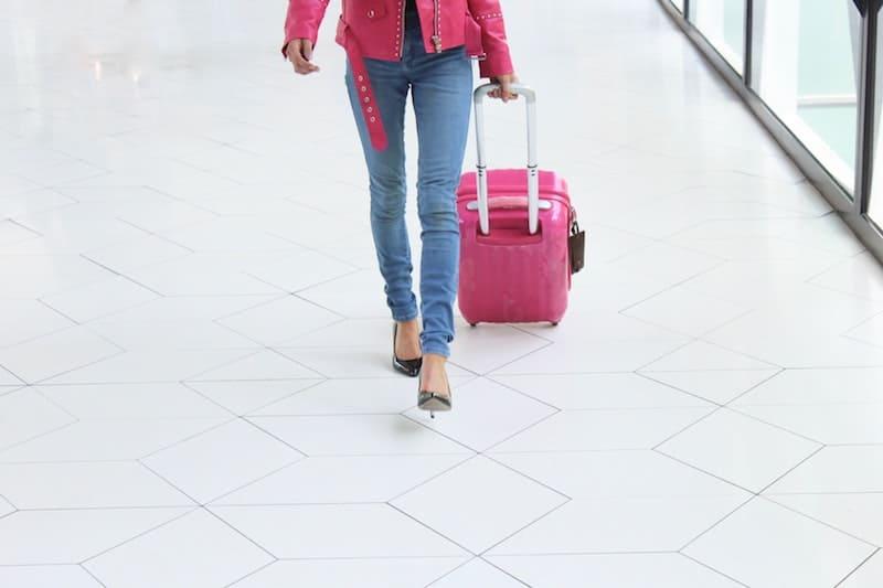 Mujer llevando una maleta rosa
